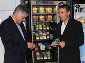 Miguel Calahorrano (izda.), Embajador de Ecuador en España, junto a Javier Fernández, Director de Copade, junto a la máquina expendedora de chocolate.